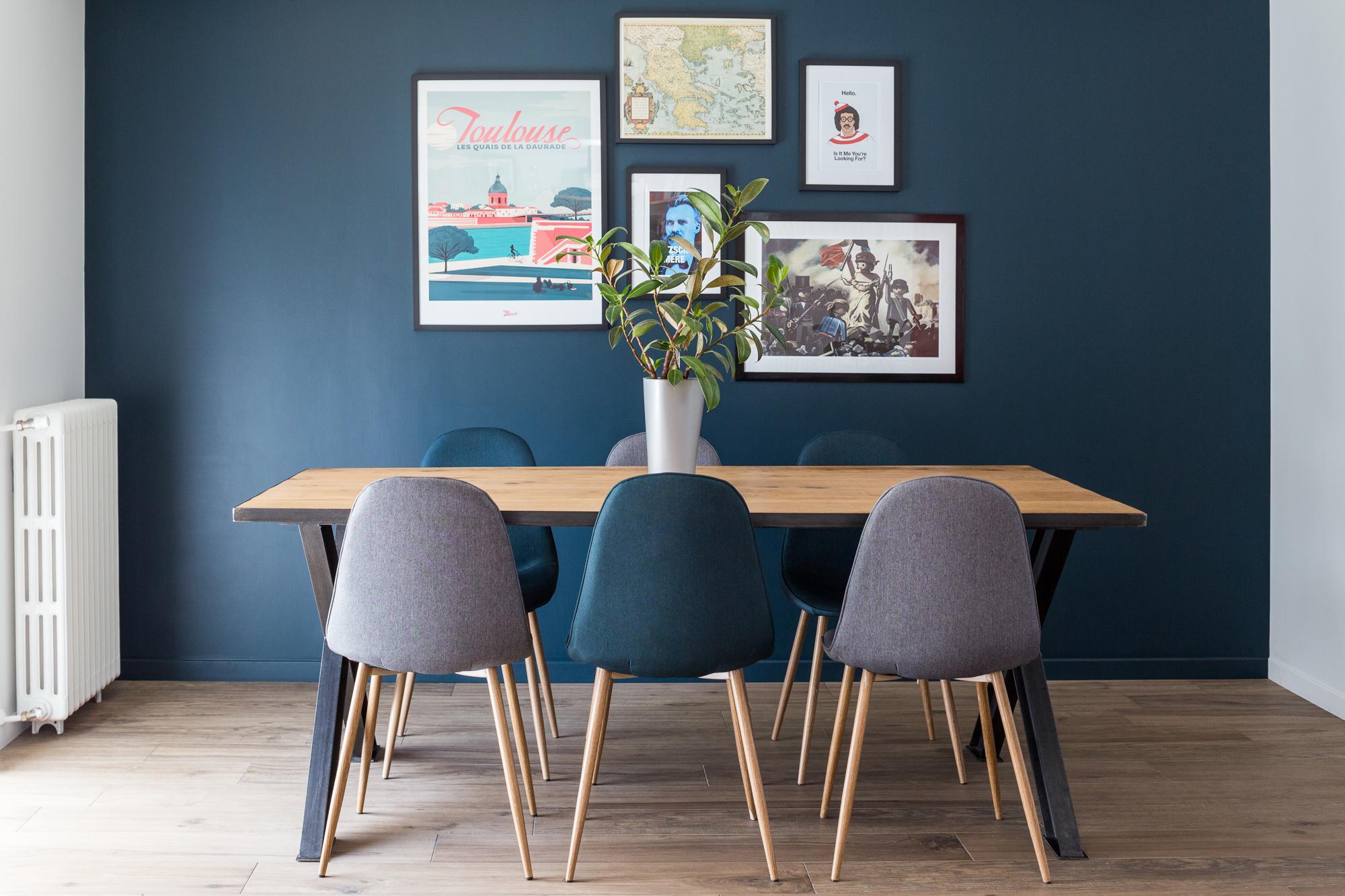 Table de salle à manger avec des chaises assorties et des cadres au mur
