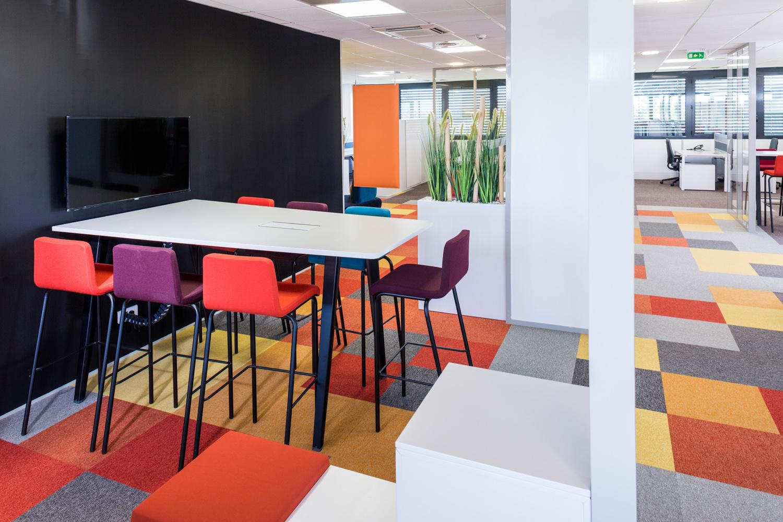 Photographie d'ensemble de l'open space du bâtiment Apsys à Blagnac avec sa moquette colorée