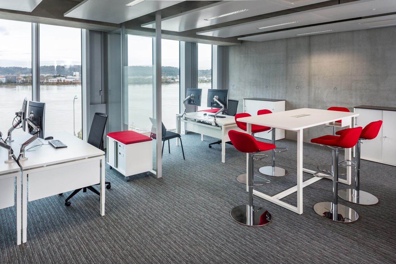 Mélange d'Open Space et d'espace de coworking, avec ses chaises hautes rouges et ses espaces de travail complet.