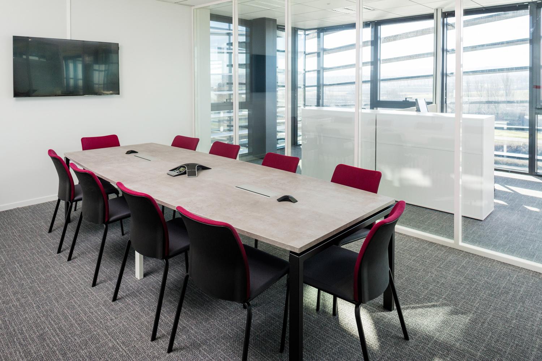 Une salle de réunion avec un grand écran TV et des chaises rouges