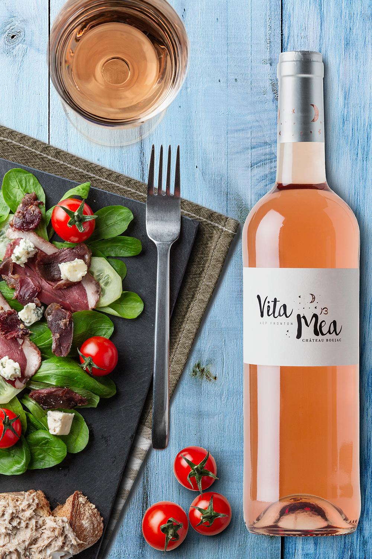 Photographie d'une bouteille de vin rosé mis en situation dans le studio photo d'Antoine Heusse avec une salade.