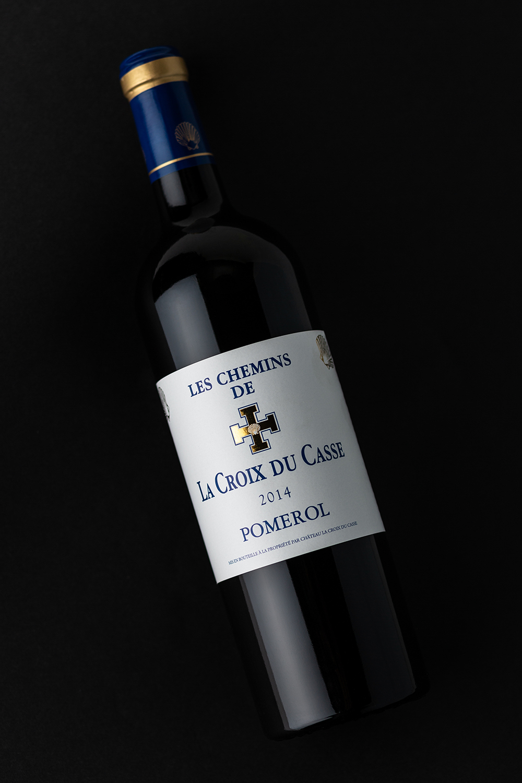 Photographie d'une bouteille de vin rouge sur fond noir