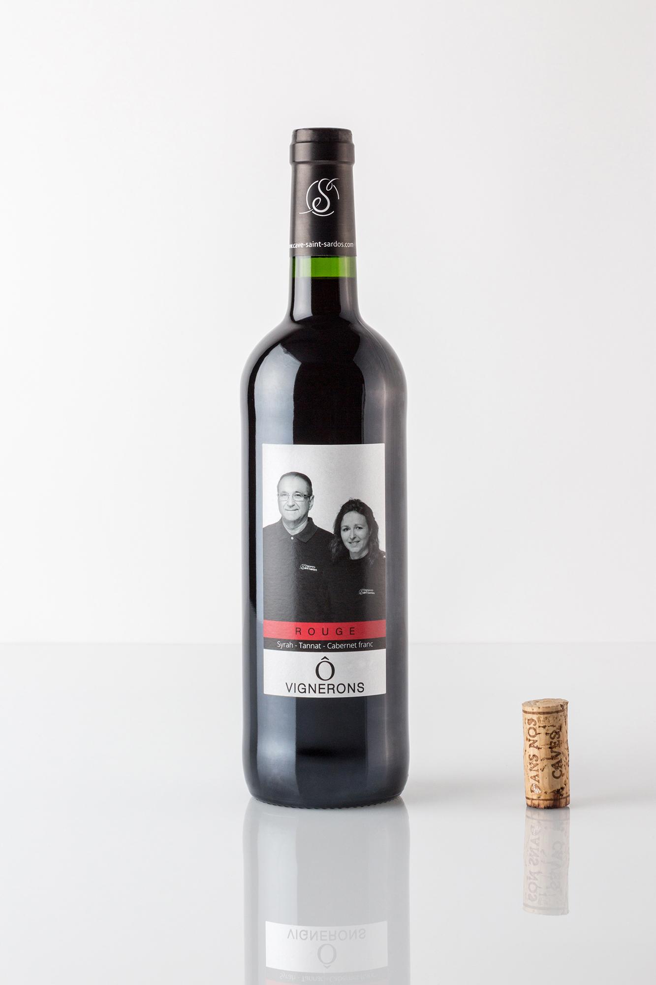 Bouteille de vin rouge sur fond blanc avec un bouchon à côté