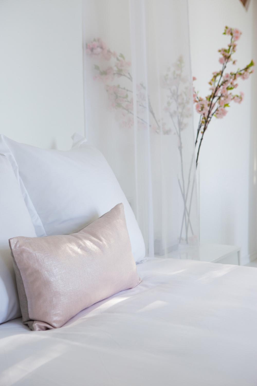 Détail de lit avec un coussin blanc