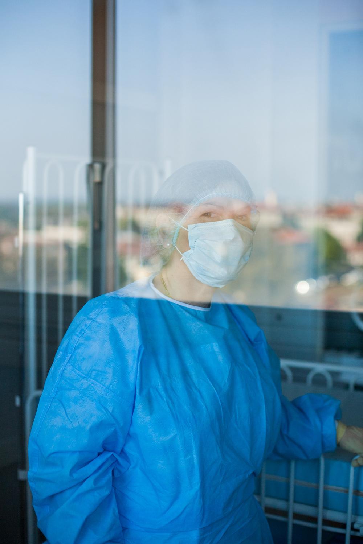 Une infirmière dans une salle stérile pose à travers la vitre. On voit Toulouse dans le reflet de la vitre