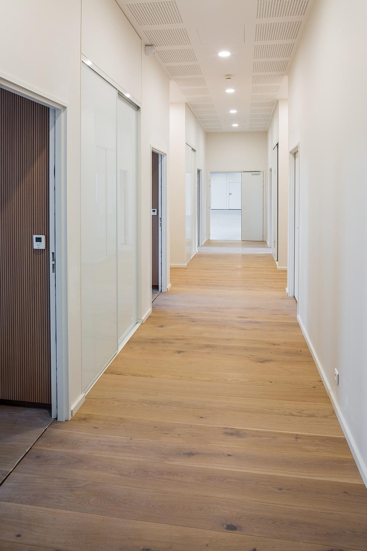 Un couloir avec un parquet en bois qui dessert différents bureaux