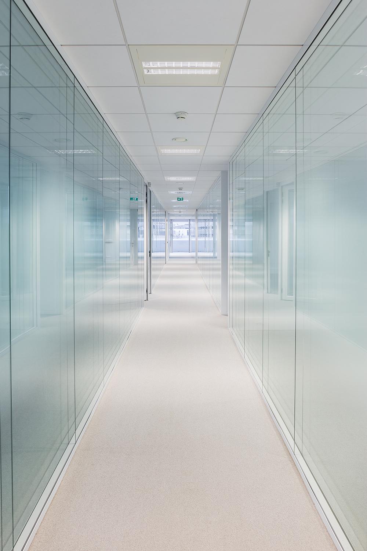 Un long couloir avec des vitres de chaque côtés dans le bâtiment Safran