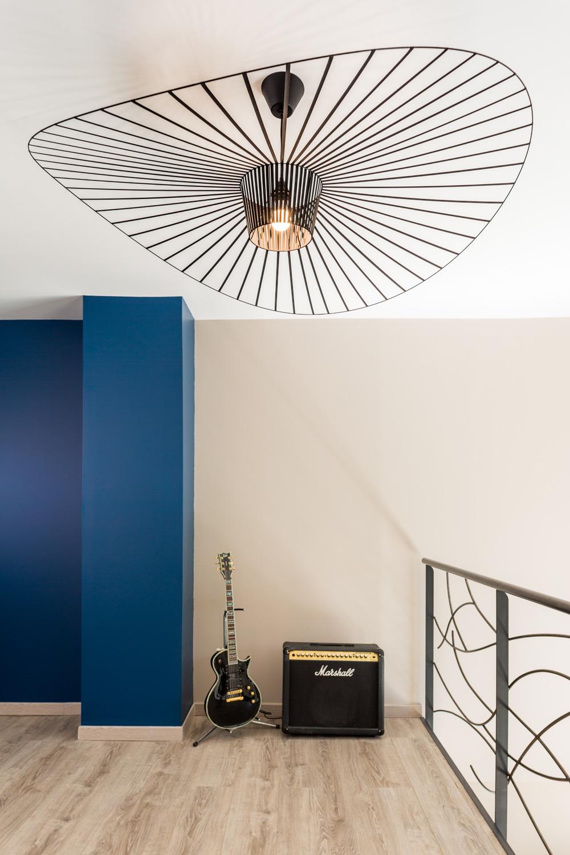 Grand lustre en métal avec une guitare et son ampli dans une maison