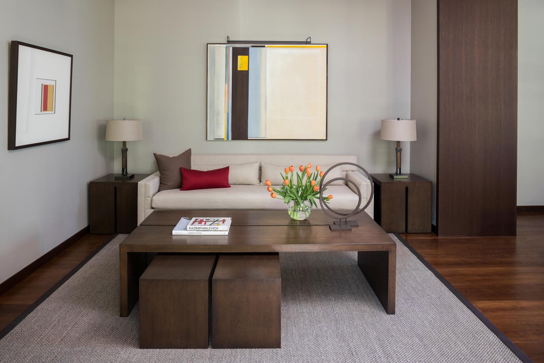 Table basse en bois et peintures abstraites au mur