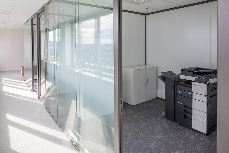 Couloir avec la vue qui se reflète dans les murs vitrés avec un accès à la photocopieuse
