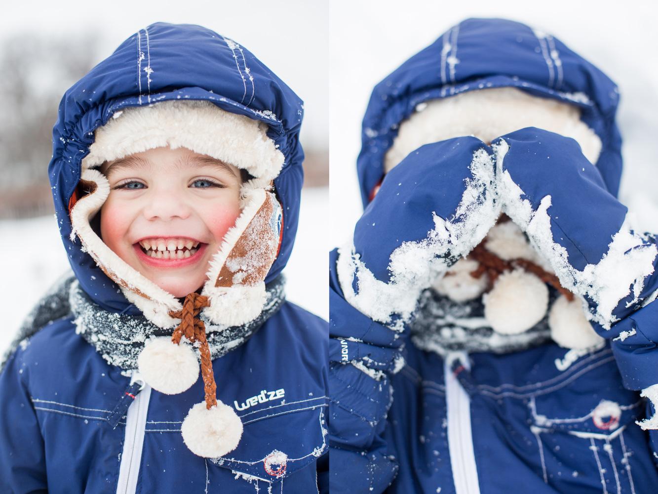 Portrait d'un enfant bien couvert dans la neige qui joue avec le photographe