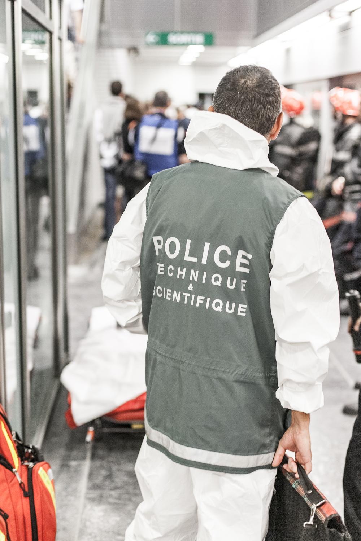 Un policier technique et scientifique de dos, avec un gilet, participe à l'exercice plan rouge dans une station du métro de Toulouse