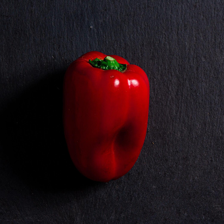 Un poivron rouge sur une ardoise