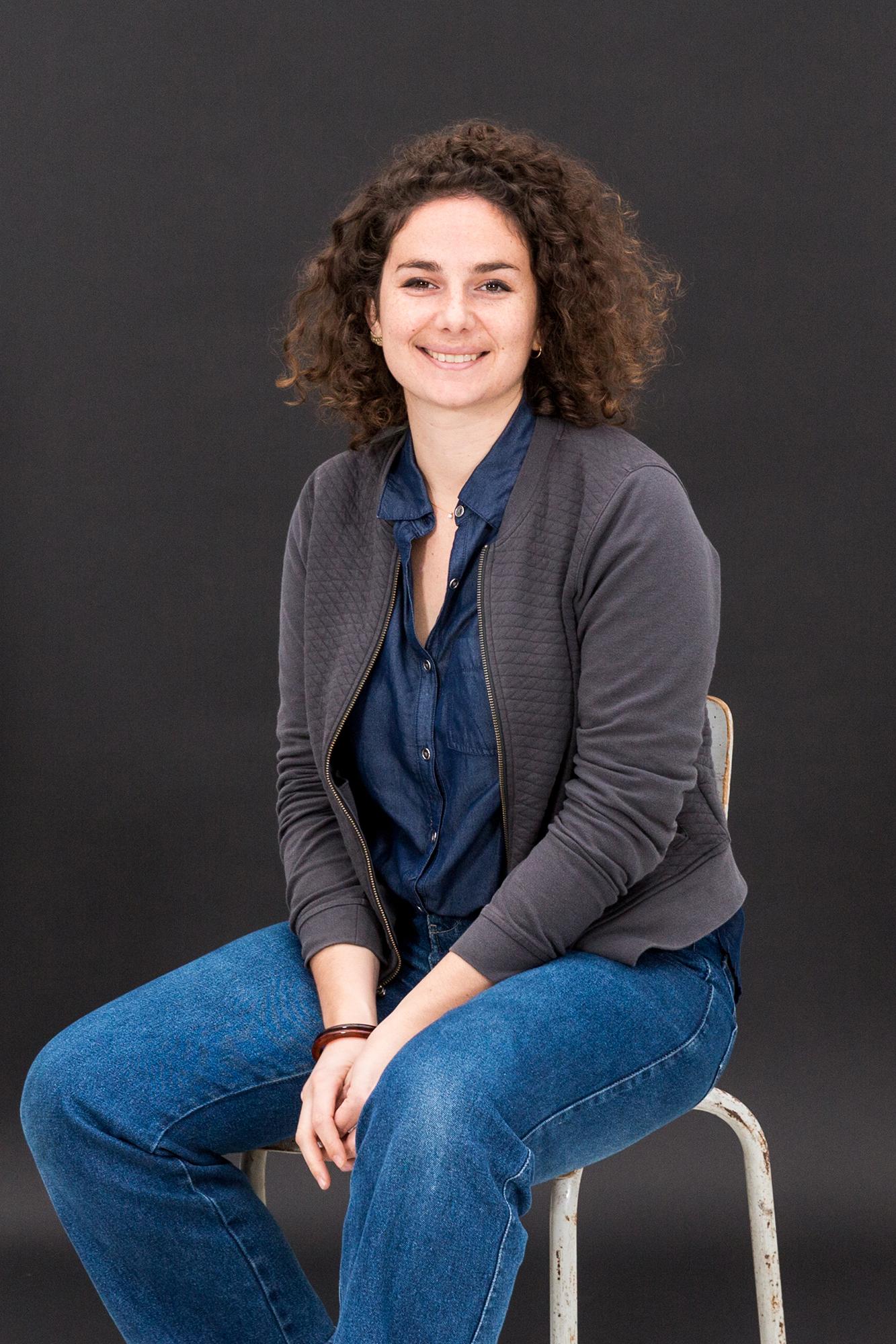 Portrait d'une employée sur une chaise devant un fond noir