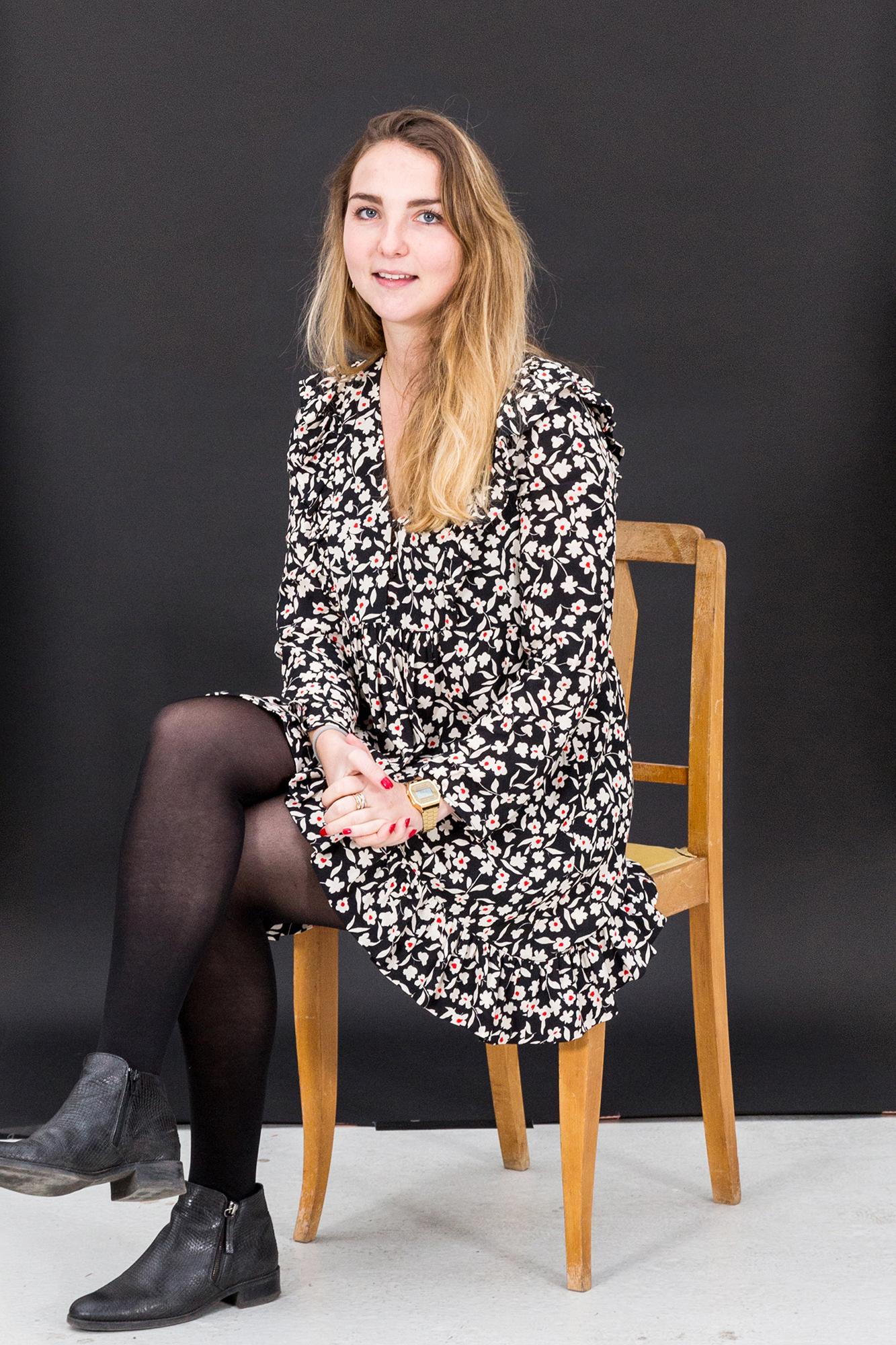 Portrait d'une collaboratrice sur un fond noir assis sur une chaise