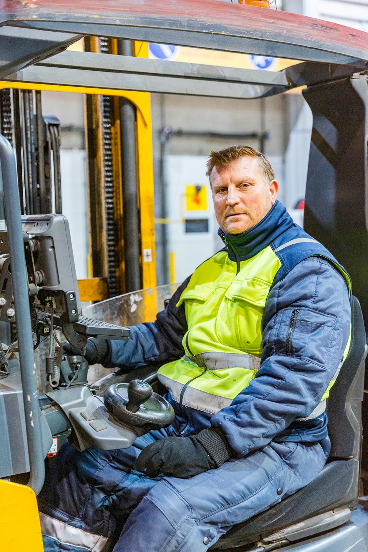 Un employé cariste pose avec son chariot dans l'entrepôt de DHL Supply Chain pour la communication d'entreprise
