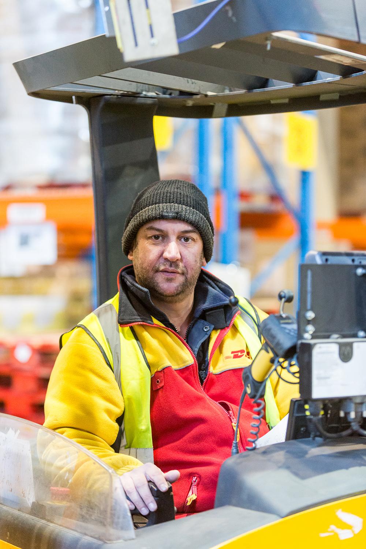 Un employé cariste sur son chariot chez DHL Supply Chain sans un entrepôt