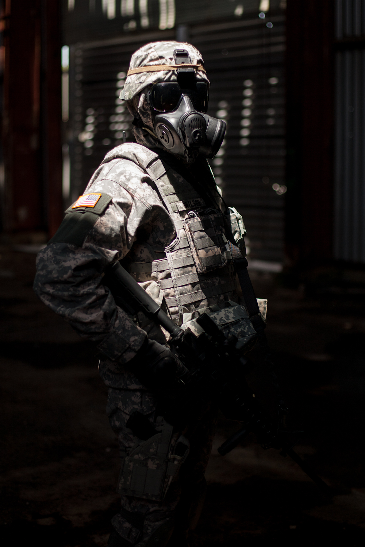 Un militaire équipé dans un hangar, avec un rayon de lumière sur lui