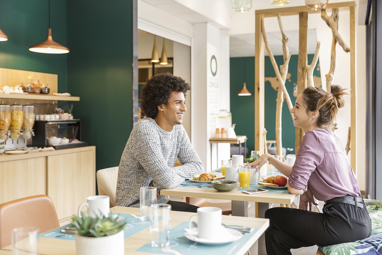 Photographie publicitaire pour un hôtel avec un couple pendant le petit déjeuné.