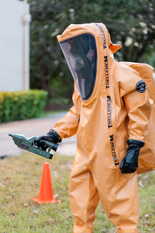 Un employé de Proengin pose pour une séance photo en combinaison BNC et l'équipement technique