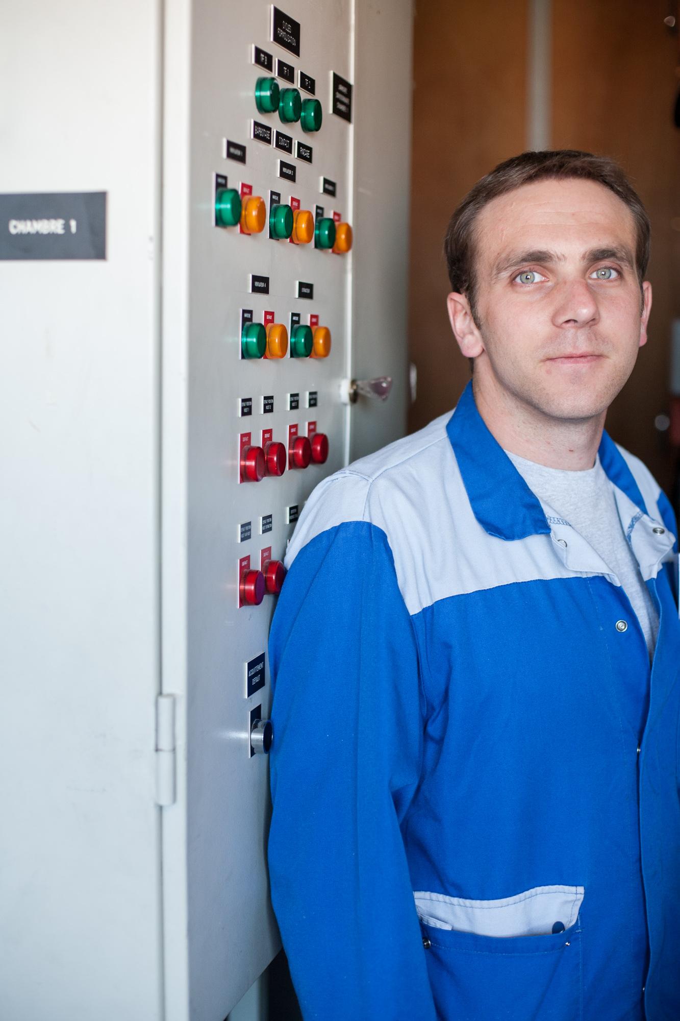 Portrait d'un technicien devant une console technique