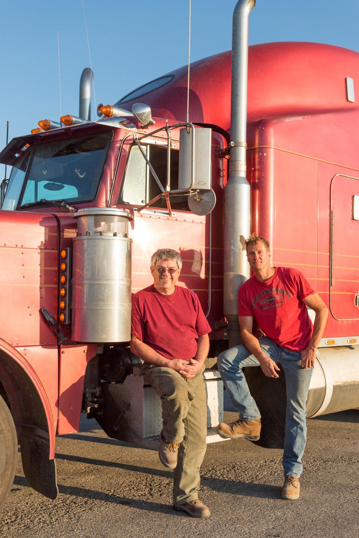 Deux camionneurs posent pour la photo devant un camion