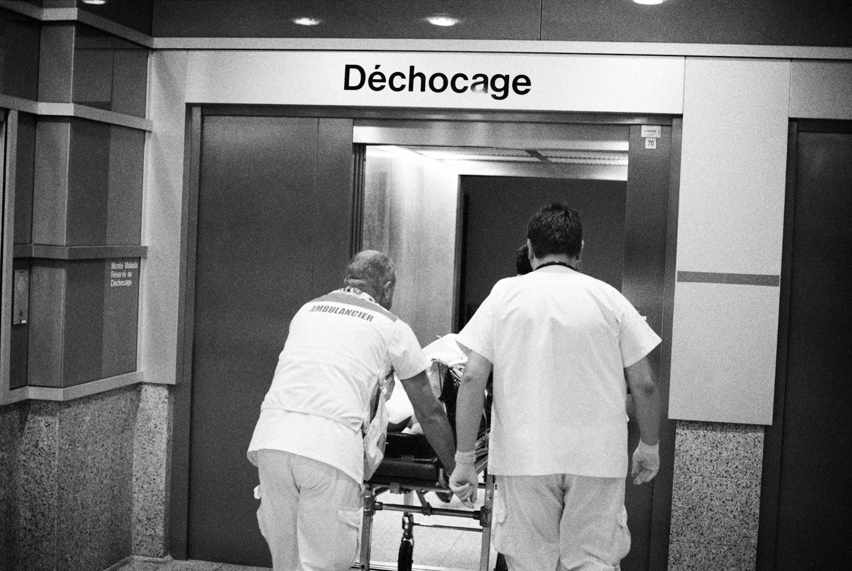 L'équipe du SAMU31 arrive au service des urgences du CHU de Toulouse. Ils entrent dans l'ascenseur qui mène au déchocage avec un blessé.