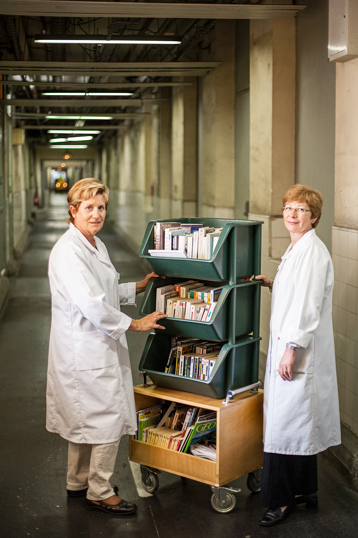 Deux femmes posent pour la photo de l'hôpital du CHU de Purpan avec le charriot de livre pour la distribution