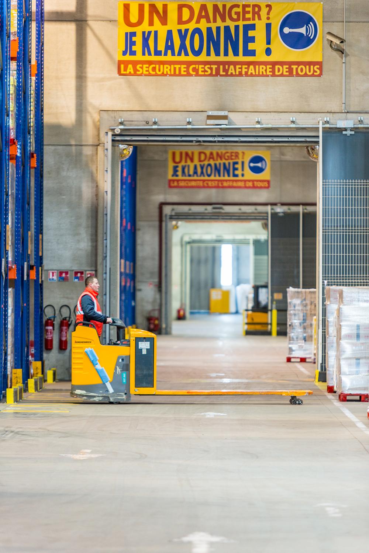 Un charriot au milieu d'un long couloir dans un entrepôt de stockage