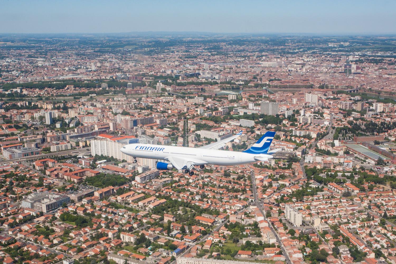 Prise de vue aérienne d'une Airbus A330 devant la ville de Toulouse en arrière plan