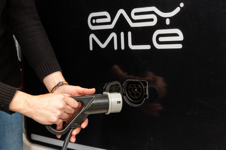 Une personne branche la prise du véhicule EZ10 d'Easymile