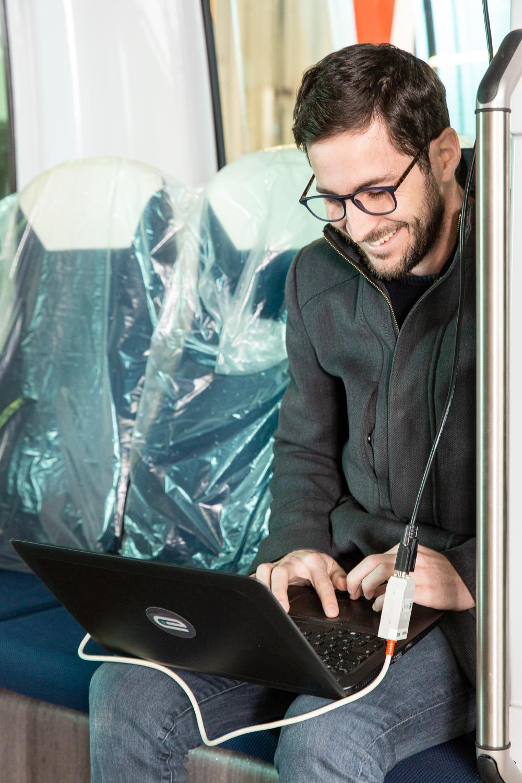 Un employé programme le logiciel du véhicule Easymile depuis son ordinateur portable. Il est assis dans le véhicule.