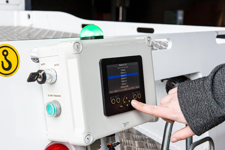 Une main actionne des boutons sur une petite console du véhicule EZ10 de Easymile