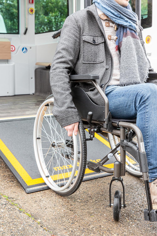 Une personne en fauteuil roulant utilise la rampe pour accéder au véhicule Easymile ES10