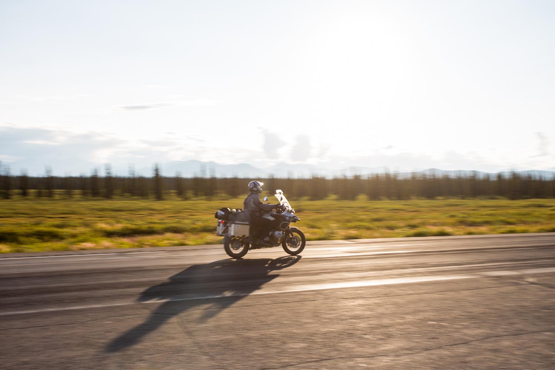 Une moto roule sur une route en Alaska au soleil couchant