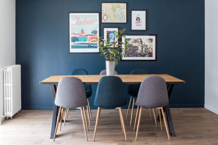 table avec chaises devant un mur bleu et ses cadres décoratifs