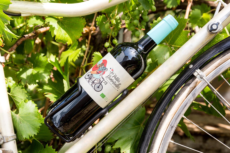 Une bouteille de vin rouge placé sur un porte gourde d'un vélo devant des vignes.