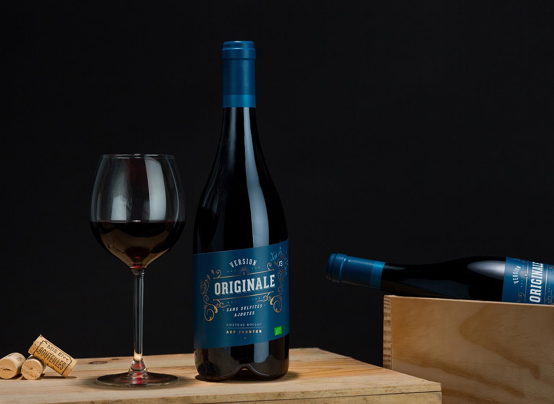 Bouteille de vin rouge sur une caisse en bois de vin, avec un verre de vin rouge sur le côté.