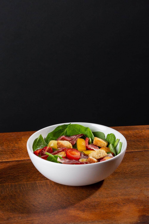 Un bol blanc avec une salade composée, sur une table en bois et un fond noir. Photo de studio.