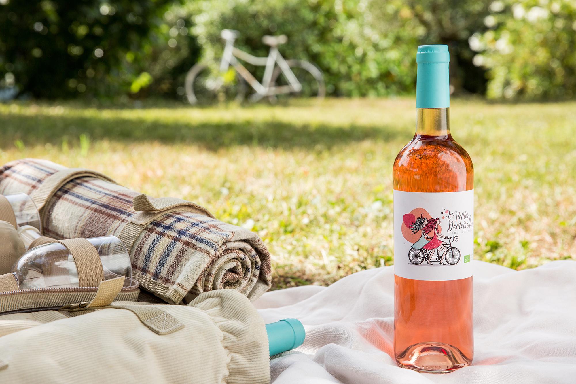 Une bouteille de vin rosé posée sur une nappe de pique-nique. On voit un vélo en arrière plan.