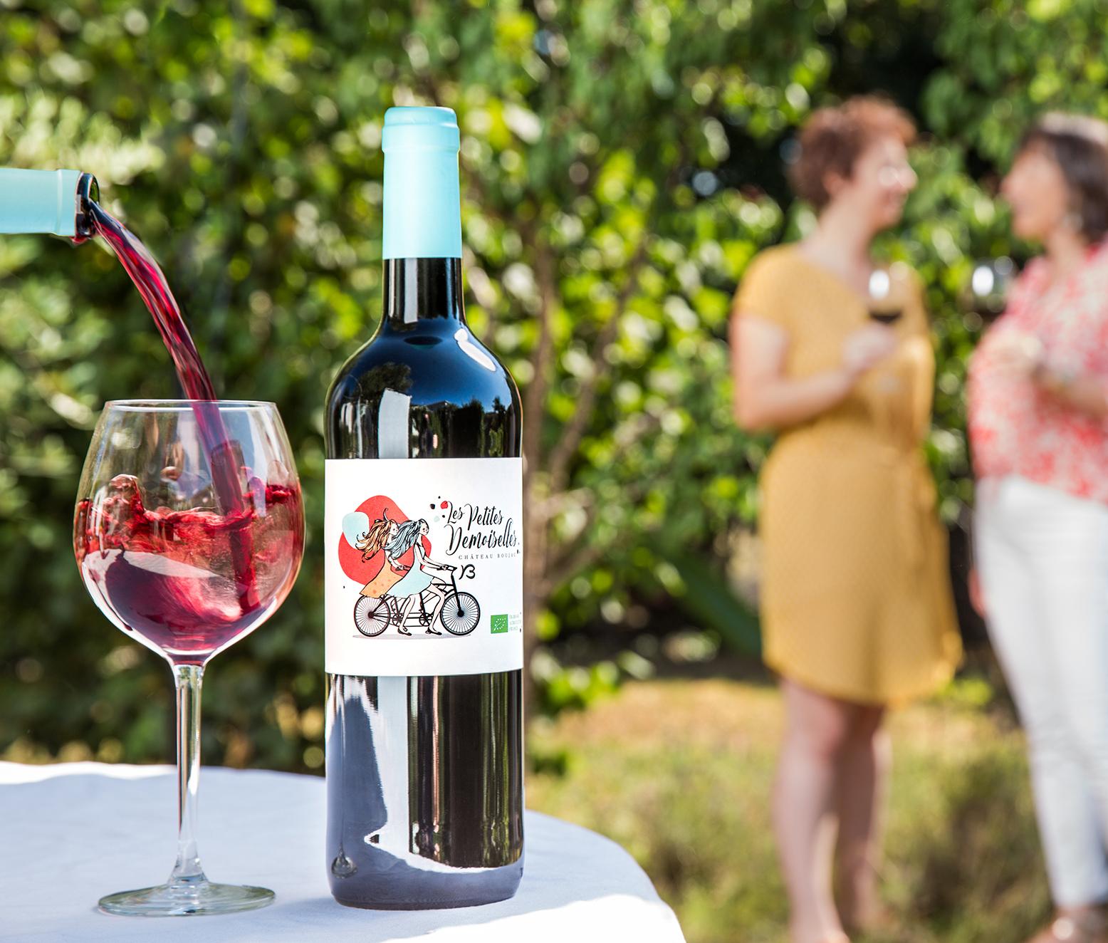 Verre de vin en train de se remplir avec le mouvement du vin dans le verre. Deux personnes discutent en arrière plan.