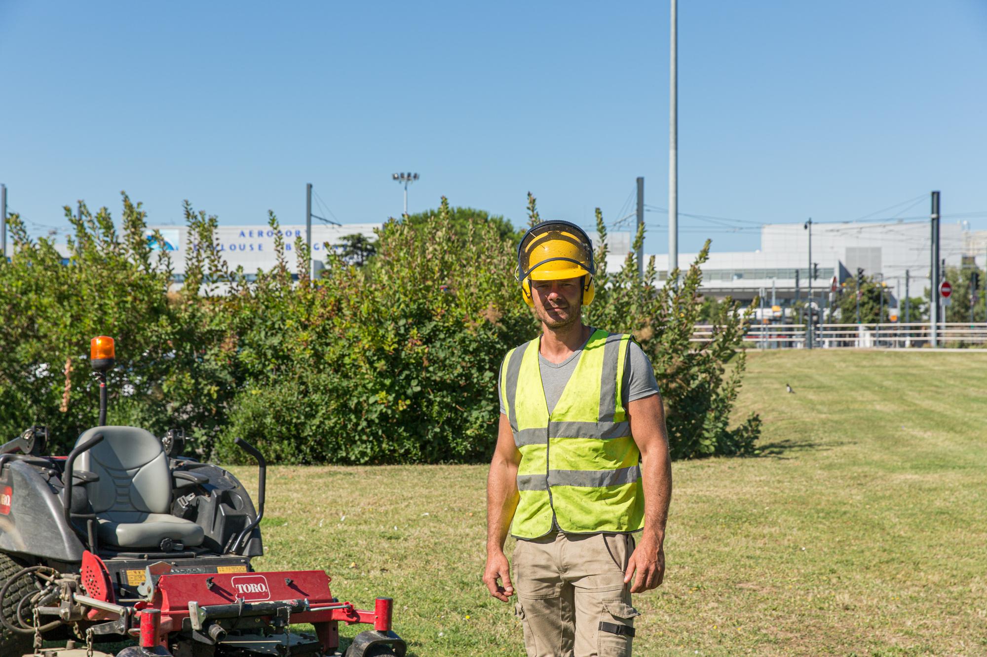 Un employé se tient  à côte de la tondeuse autoporté pour un portrait. On aperçoit l'aéroport de Toulouse Blagnac en arrière plan