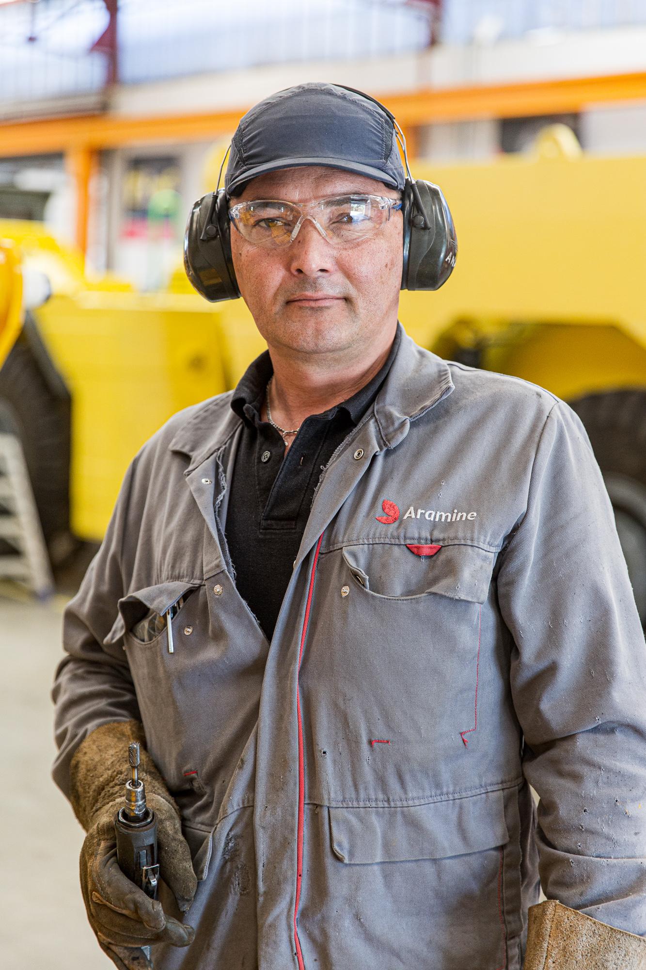 Un technicien d'atelier chez Aramine avec ses outils dans le hangar