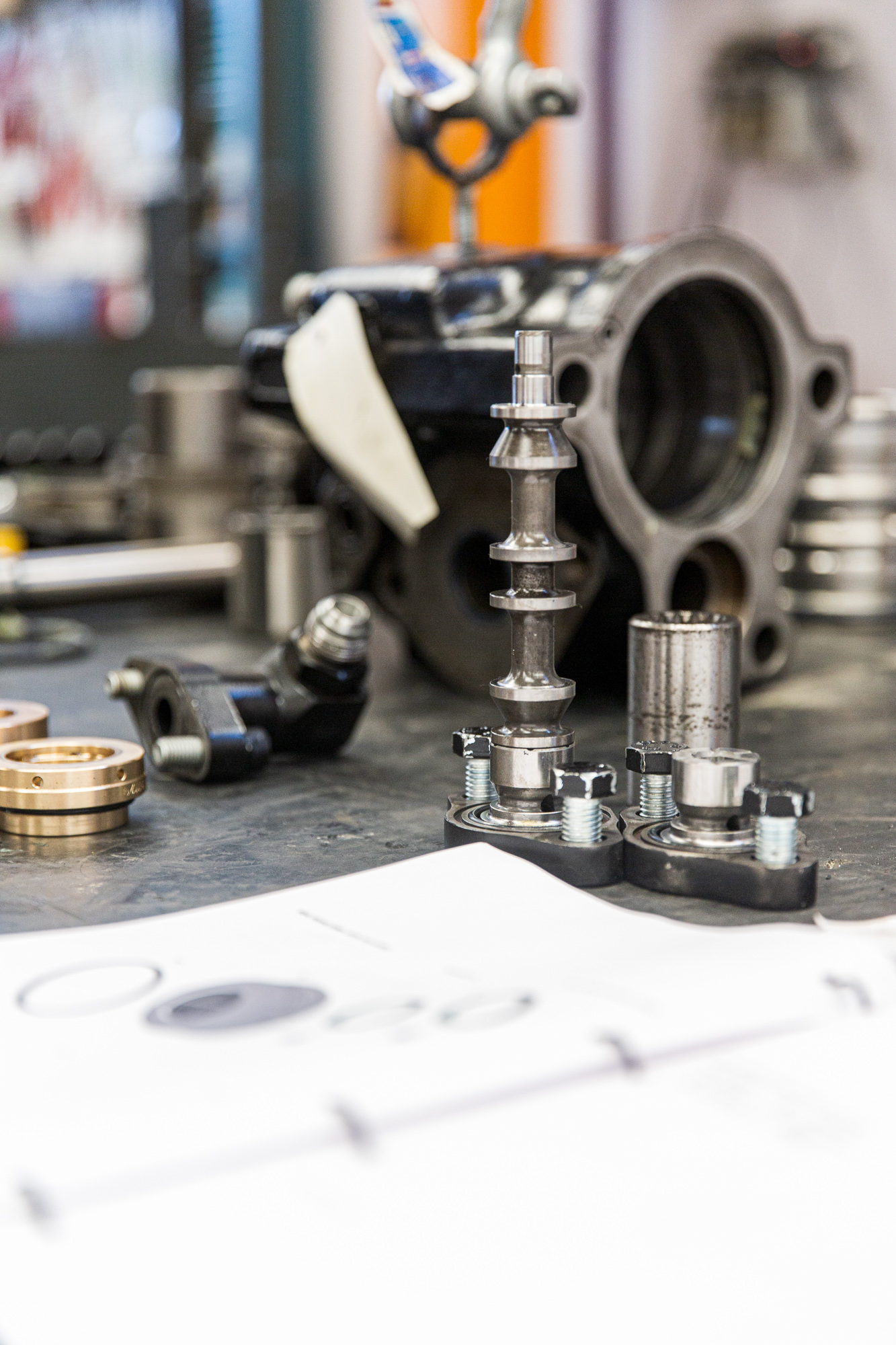 Un plan de montage est ouvert sur une table. On voit les pièces mécaniques en arrière plan.