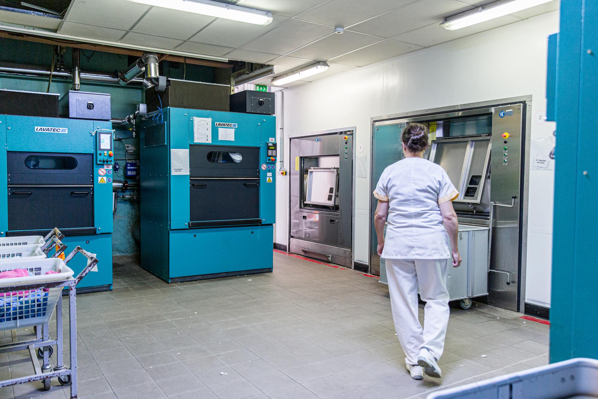 Une employé de la blanchisserie industrielle marche dans le pièce des machines