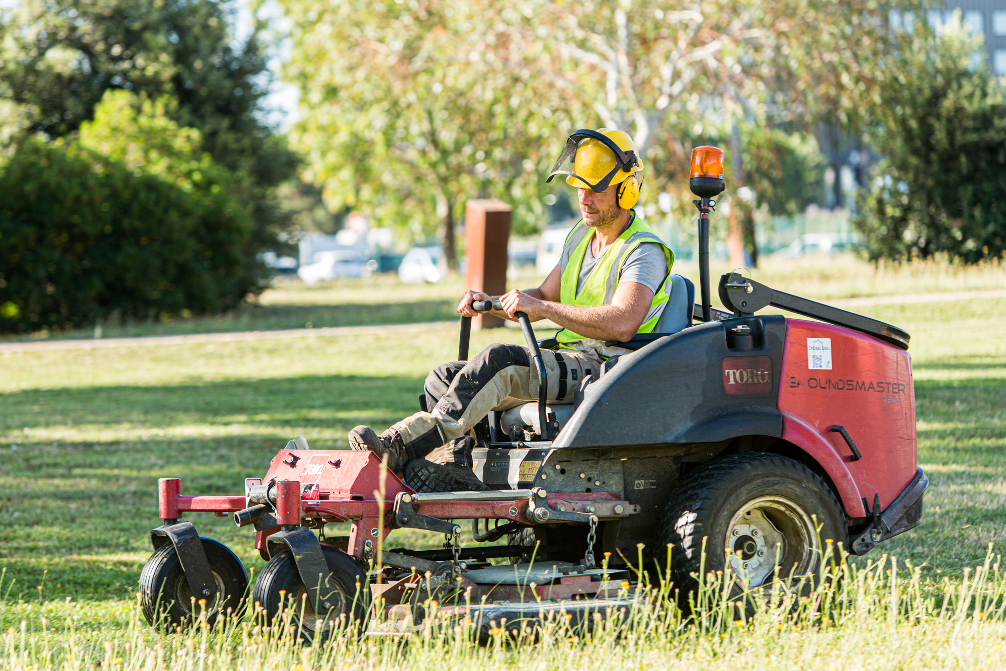 Un employé utilise la tondeuse autoporté pour couper l'herbe