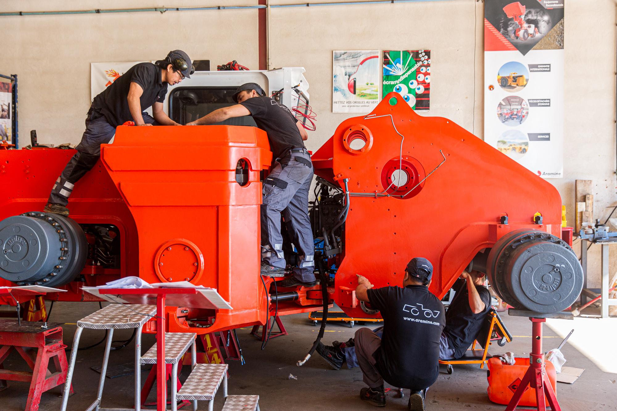 Trois mécaniciens travaillent sur un véhicule de la société Aramine. Reportage photo pour la société