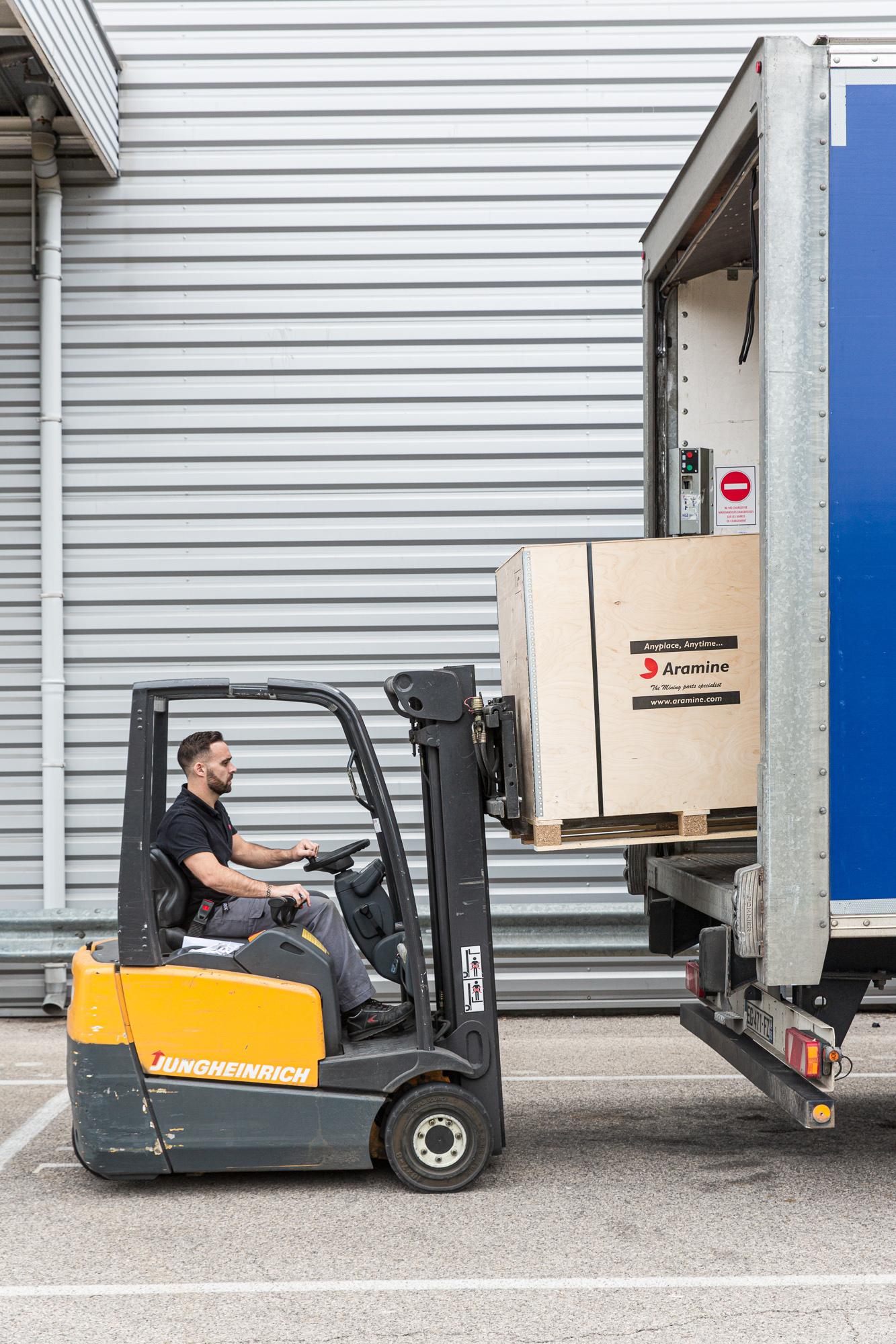 Un charriot charge un camion avec une grosse caisse en bois. Il est inscrit Aramine sur la caisse en bois.