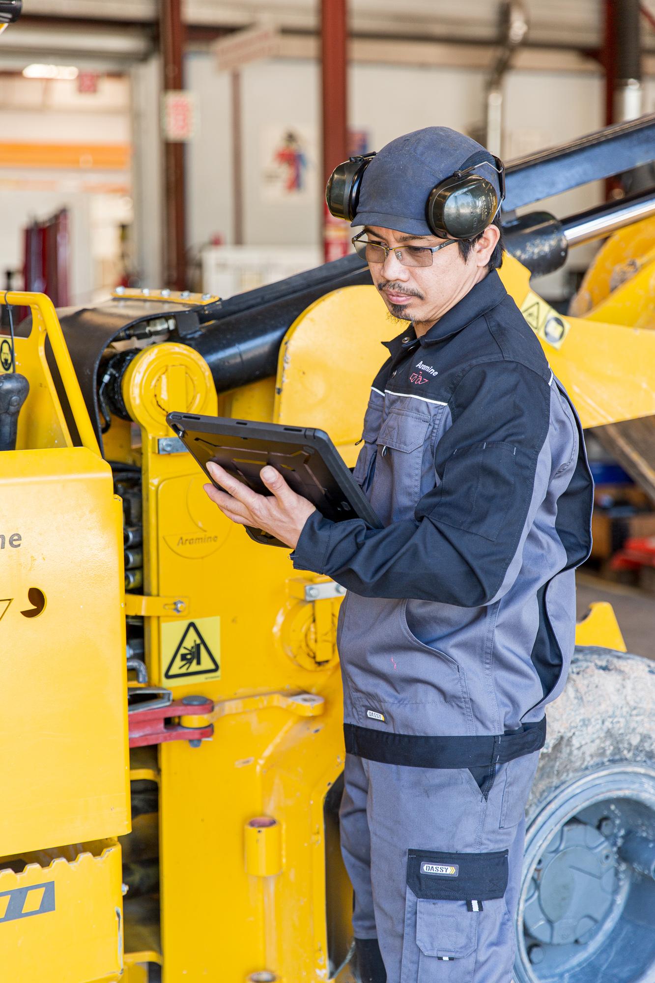 Un employé avec une tablette inspecte un véhicule chez Aramine. Photographies pour un reportage industriel