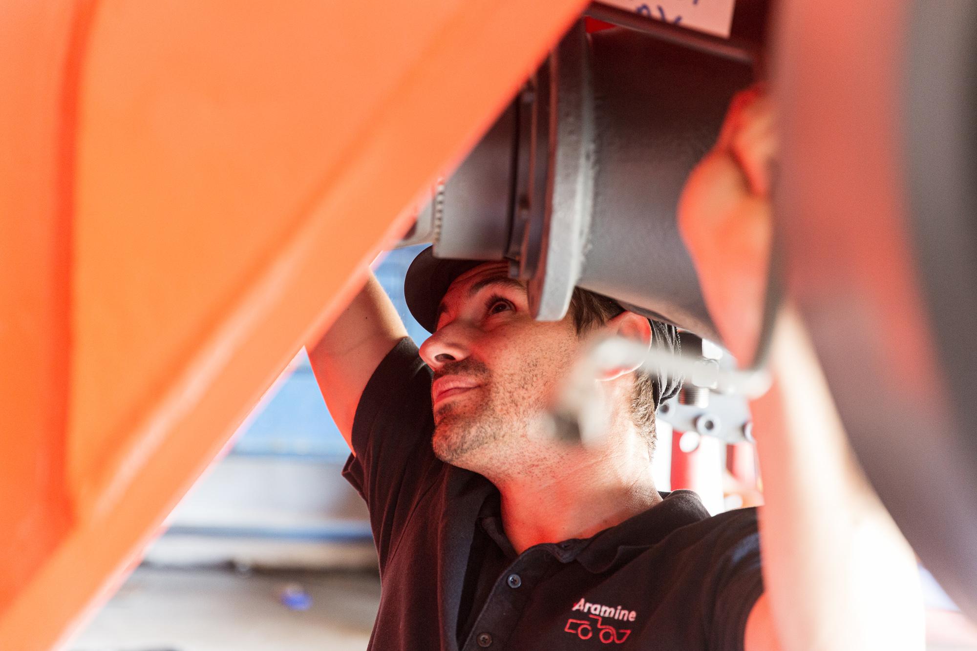 Un mécanicien en-dessous d'un véhicule travaille à sa réparation
